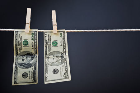 money laundering: American currency. USA money, Dollar bills hanging on rope attached with clothes pins.