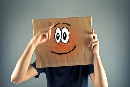 Man with cardboard box on his head with happy face expression just realized something. photo