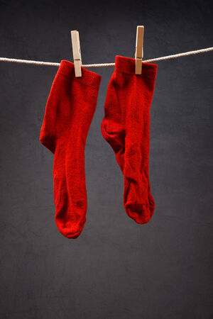 clothespins: Old red socks hanging on rope attached with clothespins to dry.