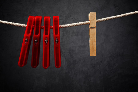 singular: Clothes pins on the rope. Wooden one is Standing out from the crowd.