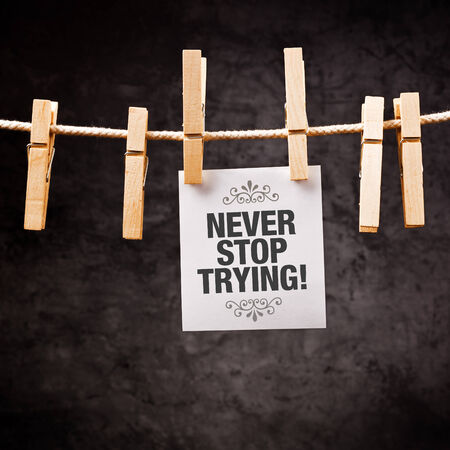 Never Stop Trying motivational message printed on note paper and hanged on clothesline with pins. photo