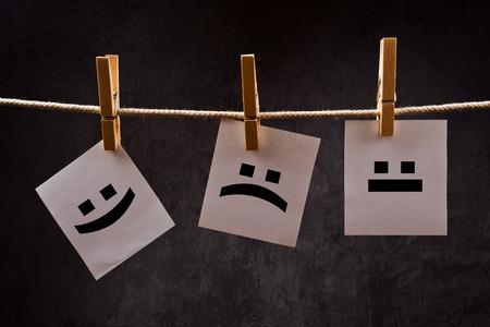 cara triste: Emoticones impresas en papel de nota attched a la cuerda con ganchos de ropa - feliz, triste y neutral.