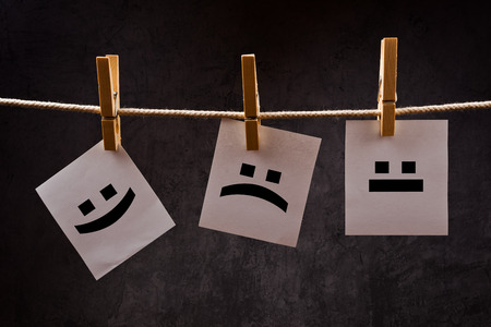 neutral: Emoticons printed on note paper attched to rope with clothes pins - happy, sad and neutral.