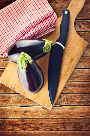 Eggplant or Aubergine with knife on wooden chop board photo