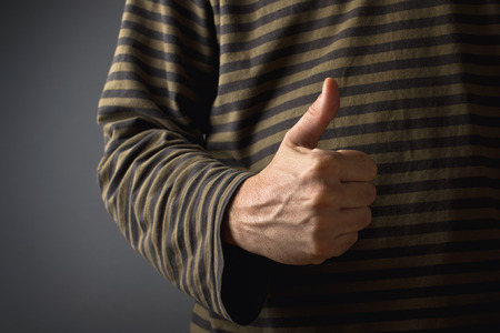 endorsement: Casual man giving thumb up as endorsement or approval gesture.