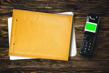 cordless phone: Wireless cordless phone and blank envelope with copy space on wooden tabletop. Stock Photo
