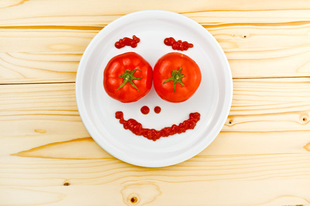making face: tomatoes and ketchup making smiley face served on a white plate on wooden table. Stock Photo