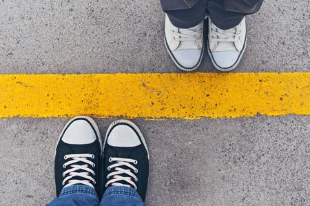 Sneakers van boven. Mannelijke en vrouwelijke voeten in tennisschoenen van boven, die zich op scheidingslijn. Stockfoto