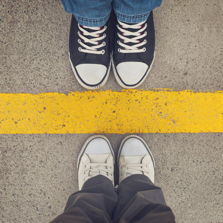 boundary: Sneakers from above. Male and female feet in sneakers from above, standing at dividing line. Stock Photo
