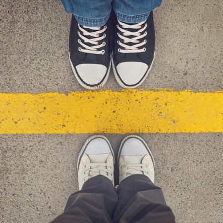 scheidingslijnen: Sneakers van boven. Mannelijke en vrouwelijke voeten in tennisschoenen van boven, die zich op scheidingslijn. Stockfoto