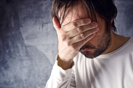 remorse: Depressive man crying with hand covering his face, looking upset and showing remorse