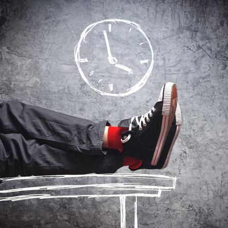 jaunty: D�a de trabajo final. Hombre perezoso en zapatillas de deporte con las piernas sobre la mesa, pocos minutos hasta el final de sus horas de trabajo.