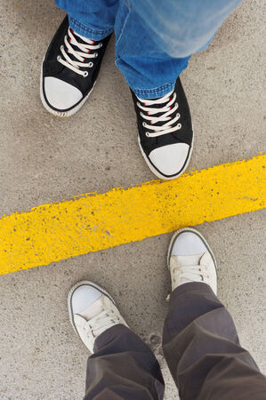 Sneakers from above. Male and female feet in sneakers from above, standing at dividing line. Stock Photo