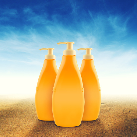 Bottles of sunbath oil or sunscreen on hot beach sand in summer  photo