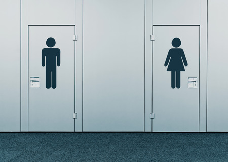 sex discrimination: Ladies room and mens room. Closed toilet doors with printed marks.