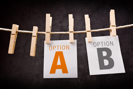 think different: Concept of choice between two options marked as A and B. Letters are printed on note paper and attached to crope with clothes pins. Stock Photo