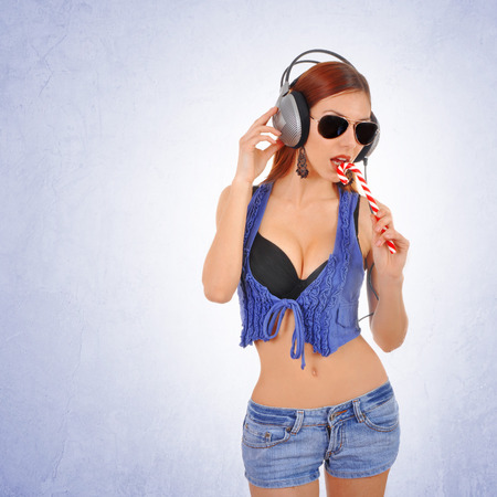Sexy young woman licking lollipop while listening to the music on headphones. Careless urban youth hipster woman. photo
