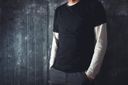 スリムな背の高い男のテキストやデザインのためのコピーのスペースとして空白の黒い t シャツでポーズします。