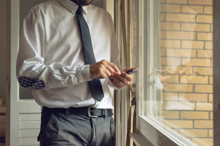 Businessman taps mobile smart phone, standing close to office window. photo
