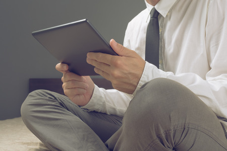 Businessman holding digital tablet computer, browsing internet while sitting on a bed in hotel room  photo