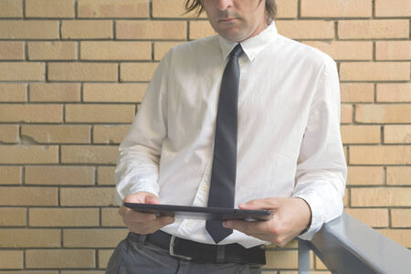 yellow wall: Businessman holding digital tablet computer, standing at the office balcony with yellow brick wall