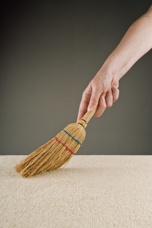 brooming: Female hand is sweeping carpet with short handle broom Stock Photo