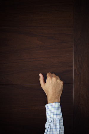 knocking: Male hand is knocking on wooden door Stock Photo