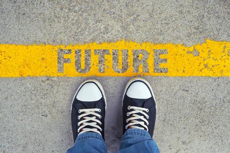 黄色の線と未来のタイトルのアスファルトの道路上の男性のスニーカー