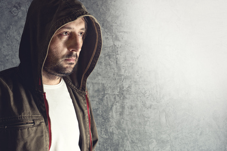 intimidating: Portrait of unshaven man wearing jacket with hoodie. Stock Photo