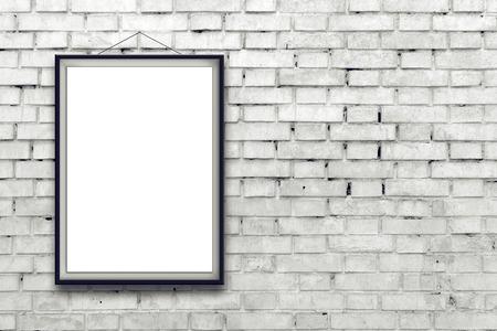 Cartel de la pintura vertical en blanco en marco negro que cuelga en la pared de ladrillo blanco Foto de archivo