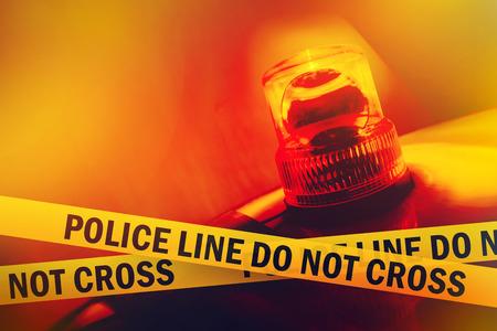 Police Line Do Not Croce Giallo fascia nastro e arancione lampeggiante e luce girevole Archivio Fotografico - 30792783