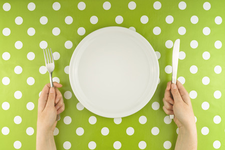 Female hands at dinner table holding fork and a knife above empty flat white plate