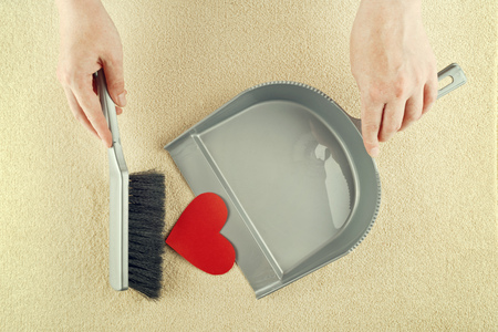 broken home: Hand sweeping heart from the floor with brush cleaner  Stock Photo