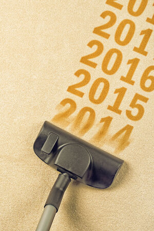 vac: Vacuum Cleaner sweeping year number 2014 from Brand New Carpet leaving sequence 2015, 2016    Happy New 2015 year concept, leaving 2014 behind for a review  Stock Photo