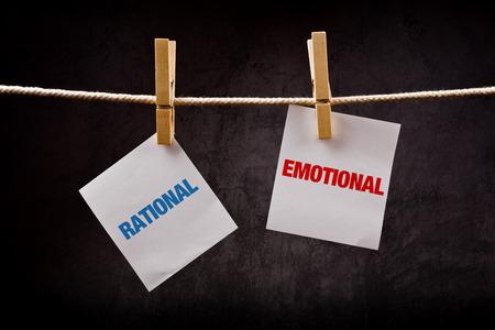 las emociones: Racional vs concepto emocional. Las palabras impresas en papel de nota y unidos a la cuerda con ganchos de ropa.