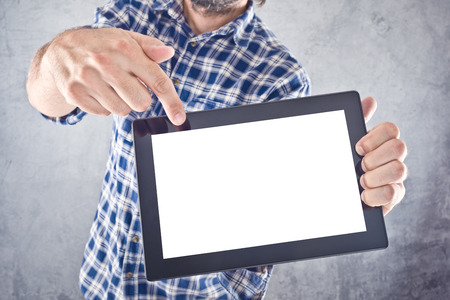 Casual man pointing to 10 inch display of digital tablet computer as copy space for your message or design. photo