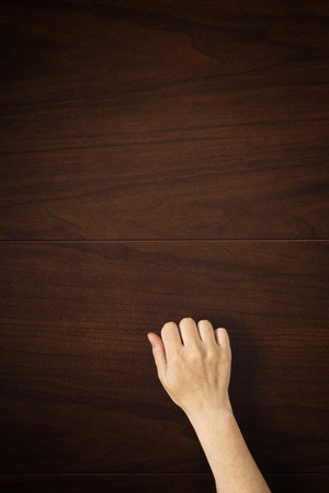 Female hand is knocking on wooden door, conceptual image. Visitor or guest is at the door. Stock Photo