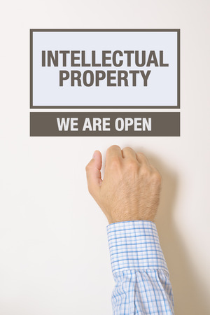 property rights: Businessman knocking on Intellectual Property Office door looking for a help or advice Stock Photo