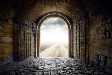 古いアーチのゲートはどこにもつながる無限の田舎道を開きます。絶望と偉大な未知の概念。