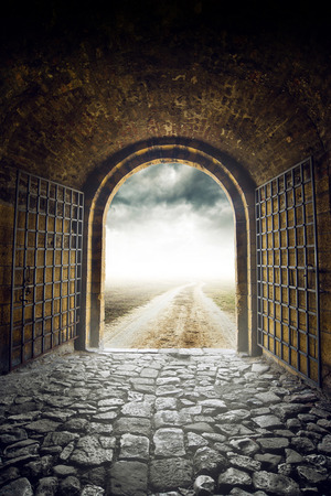 Old Arch Gate opening to Endless Country Road leading nowhere. Hopelessness and great unknown concept.