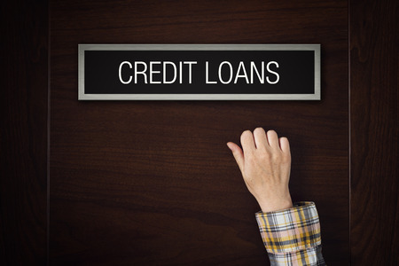 granting: Female hand is knocking on Credit Loans bank department door looking for a service