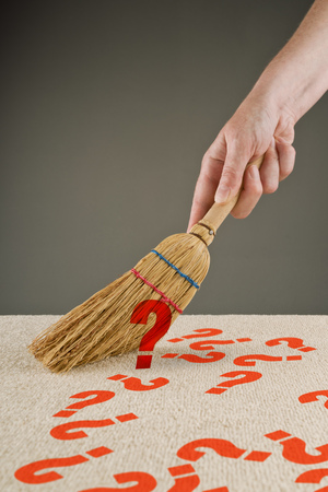 unanswered: Hand sweeping question marks from the floor with small broom Stock Photo