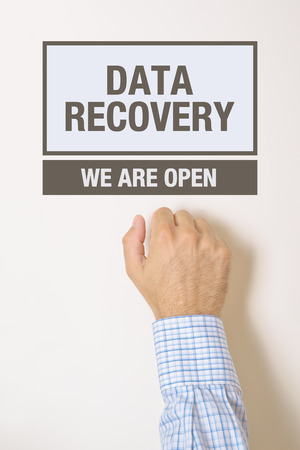 data recovery: Businessman knocking on Data Recovery Office door looking for a help service