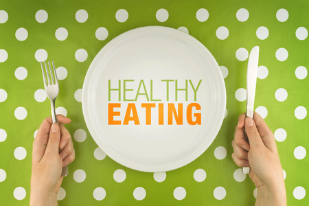 Healthy eating. Woman eating from a white flat plate, top view.