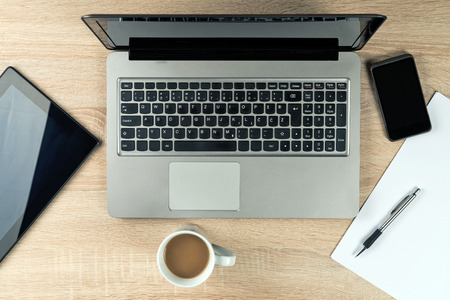 Office Table top with laptop computer, digital tablet, mobile smartphone and coffee cup.