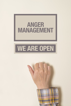 anger management: Woman hand knocking on the door of Anger Management office.
