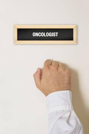 Male patient knocking on Oncologist door for a medical exam.
