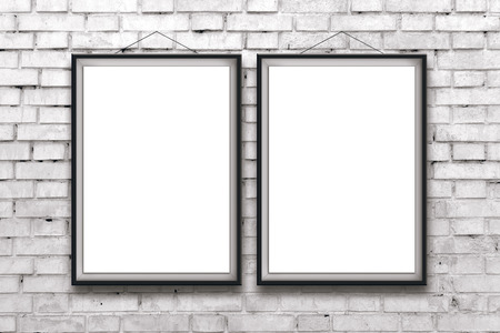 Two blank vertical painting or posters in black frame hanging on white brick wall. Painting proportions match international paper size A. photo