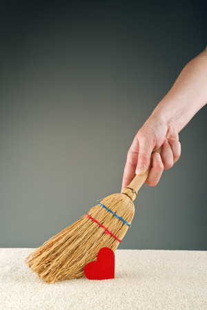 clean heart: Hand sweeping heart from the floor with short handled small broom Stock Photo