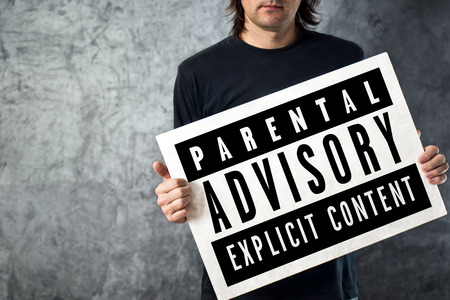 Man holding poster with Parental Advisory label printed on